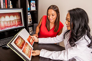 Dr. Johnson shows a patient before and afters of cosmetic dental treatments.