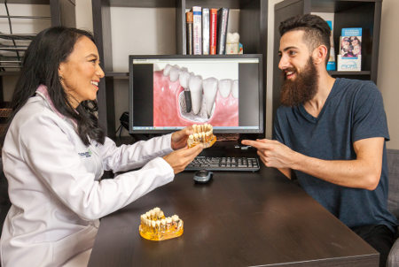Dr. Johnson shows a dental implant model to a patient during a consultation.