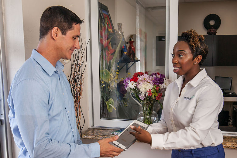 A receptionist hands a patient a tablet to fill out patient information.