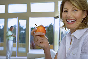 All-On-Four woman smiling as she holds an apple.,